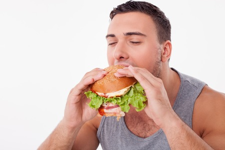 Handsome sportsman is biting a sandwich with pleasure. He closed his eyes with enjoyment. Isolated on background and copy space in left side