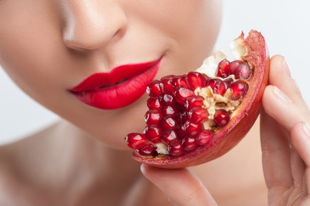 Close up of pretty woman showing a slice of pomegranate to the camera. She is gently smiling