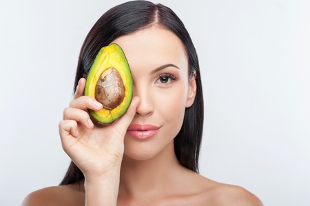 desnudo: Cheerful woman is holding an avocado and covering her eye with it. She is looking at the camera and gently smiling. Her shoulders are naked. Isolated on background