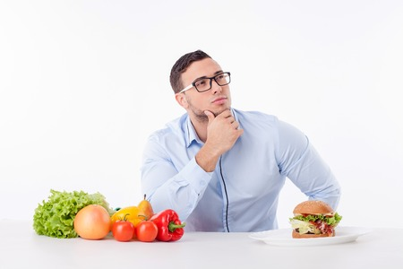 comida: Cheerful guy is sitting at the table near healthy and unhealthy food. He is thinking what to choose. The guy is looking up pensively and touching his chin. Isolated on background