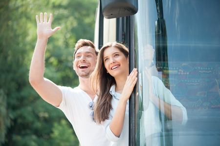 Pretty woman and man are standing in doors of the bus. They are looking through it and laughing. The boy is raising his palm and helloing with everybody