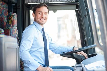 잘 생긴 버스 운전자는 스티어링 휠에 앉아있다. 그는 카메라를보고 미소 스톡 콘텐츠 - 43354848