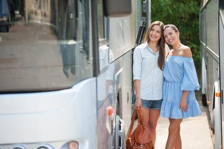 position d amour: les femmes gaies sont debout entre deux bus et d'attendre son d�part. Ils sont pr�ts pour le voyage. Les filles adoptent et souriant