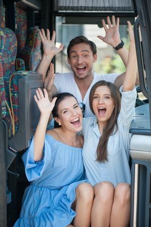 position d amour: Amis gais sont assis sur portes d'un bus. Ils l�vent la main et souriant. Les femmes se tournent. L'homme est assis derri�re eux Banque d'images