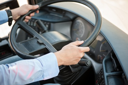steering: Close up of male hands. The driver is sitting at steering wheel of a bus