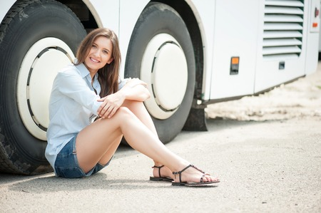 sitting on the ground: Beautiful girl is waiting for bus departure. She is sitting near the wheels of the bus on a ground. The lady is looking forward with happily and smiling. Copy space in right side