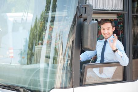 명랑 남자는 즐거움과 함께 버스를 운전. 그는 괜찮 기호 표시 및 웃 고있다. 남자는 행복과 창을 통해 찾고있다 스톡 콘텐츠