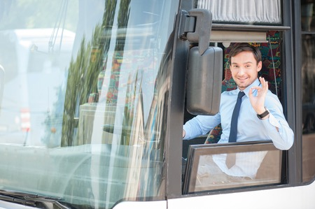 Cheerful man is driving a bus with enjoyment. He is showing okay sign and smiling. The man is looking through the window with happiness