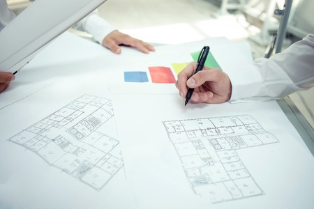 blueprint: Close up of hands of architects drawing sketches of construction. There are blueprints on the table Stock Photo