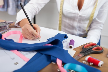 fashion  woman: Close up of hands of skilled fashion designer. The woman is sitting at the table. She is drawing sketches of clothes on a blueprint. There are many design things on the desk Stock Photo