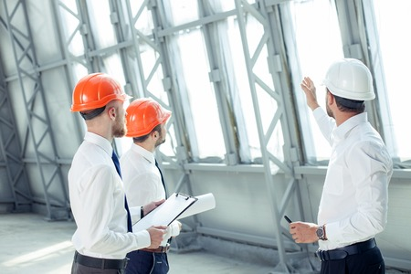 Attractive architect is explaining to the workers the plan of construction with seriousness. He is pointing his arm sideways. His colleagues are looking forward with concentration