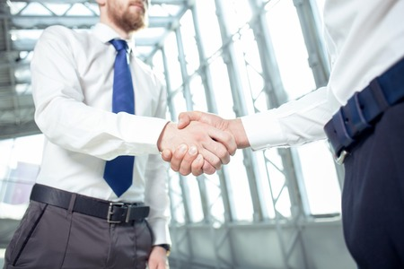 seriousness: Close up of arms of businessmen shaking hands with seriousness