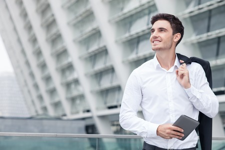 left behind: Cheerful businessman is standing and leaning on the border of building. He is holding tablet and his jacket behind his back. The worker is smiling and looking aside dreamingly. Copy space in left side