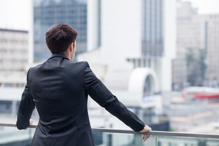 in the back: Cheerful man in suit is enjoying the view of the city from a balcony of his office. He is standing and relaxing. Focus on his back. Copy space in right side Stock Photo