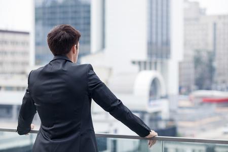 detras de: Hombre alegre en el juego que está disfrutando de la vista de la ciudad desde un balcón de su despacho. Él está de pie y relajante. Centrarse en la espalda. copia espacio en el lado derecho