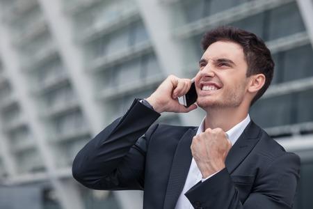 gerente: apuesto hombre de negocios est� de pie y hablar por tel�fono con su cliente. El acuerdo se llev� a cabo con �xito. El trabajador est� sonriendo y levantando el pu�o arriba feliz