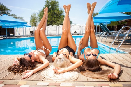 Attractive women are lying near a swimming pool and relaxing. They are sunbathing with pleasure. The friends are raising their legs up Фото со стока
