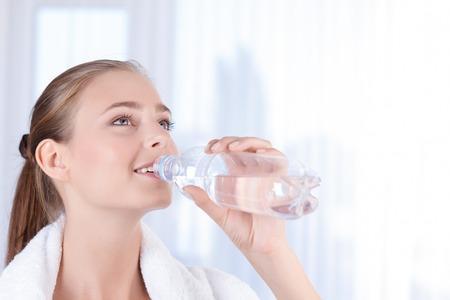 tomando agua: Abre tu mente. Hermosa dama joven y feliz celebración de la botella y el agua potable, manteniendo levantar la vista