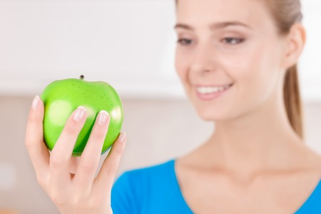 what to eat: You are what you eat. Good looking contented pleasant girl holding apple and reveling in joy while standing in the kitchen Stock Photo