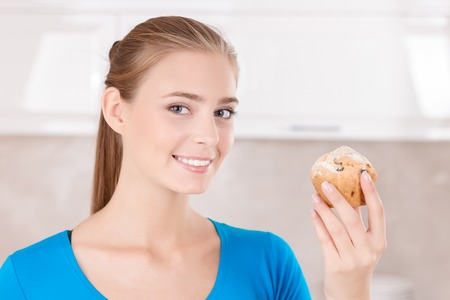 expressing joy: Eat me. Blissful smiling adorable girl holding muffing and going to eat it while expressing joy. Stock Photo