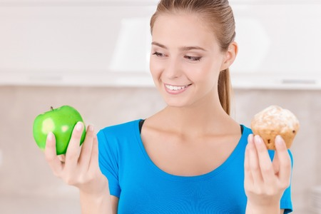 chose: What to chose. Pretty elated young woman holding apple and muffin and going to eat while standing in the kitchen.