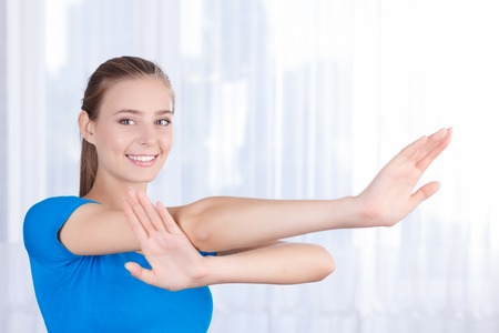 blissful: Best way to feel healthy. Upbeat nice girl holding hand lifted and doing morning exercises while feeling blissful