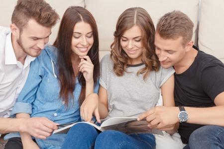 Intéressant à lire. amis joyeux agréables assis sur le canapé et la lecture de magazine en exprimer positivité.