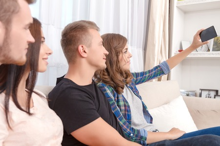 upbeat: Pictures for memories. Pleasant upbeat friends sitting on the couch and making selfie while having fun. Stock Photo