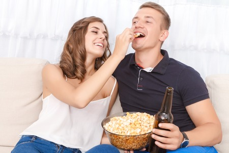 upbeat: Let me feed you. Upbeat happy young couple sitting on the couch and eating popcorn with beer while feeling delighted.