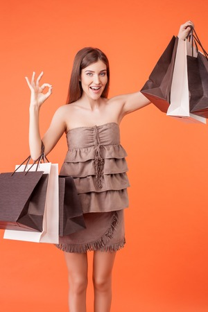 bought: Beautiful girl is going shopping with pleasure. She is showing packets of bought things. The lady is showing okay sign and smiling. Isolated on orange background Stock Photo