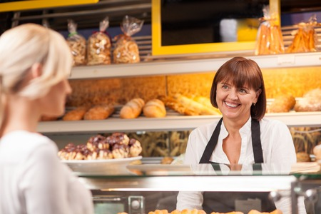 cafeterias: Professional female baker is standing at the counter in bakehouse. She is selling pastry to her client and smiling. The blond woman is buying baked products with pleasure