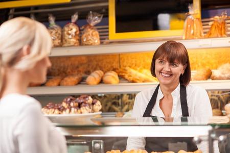 Professionele vrouwelijke bakker staat aan de balie in bakhuis. Ze is de verkoop van gebak om haar cliënt en lachend. De blonde vrouw is het kopen van gebakken producten met plezier