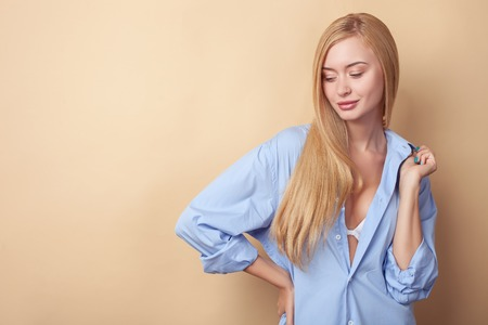 Beautiful blonde girl is posing and flirting. She is wearing a large blue shirt. The lady is smiling and looking down with desire. Isolated on brown background and copy space in left side Stock Photo