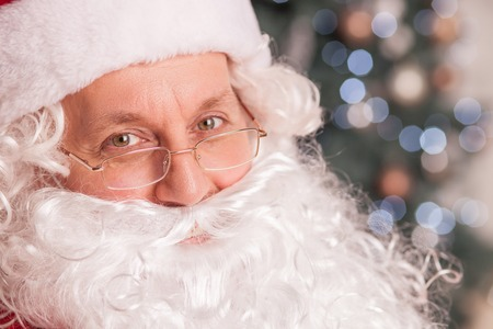 congratulating: Cheerful Santa Claus is looking forward with joy. He is congratulating everybody with New Year. The man is smiling
