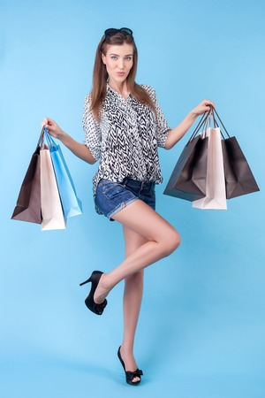boastful: Attractive styled woman is going shopping with joy. She is carrying many packets and showing it with proud. The lady is posing and looking at the camera happily