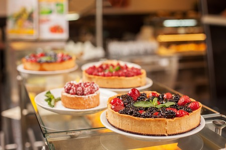 breakfast food: Close up of appetite cakes on the shelf in bakery Stock Photo