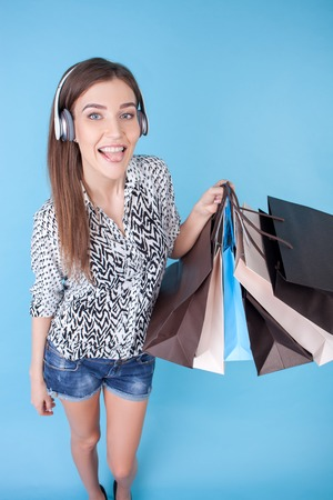 packets: Beautiful woman is listening to music from headphones. She is standing and holding many packets of bought things. The lady is showing her tongue and smiling. Isolated Stock Photo