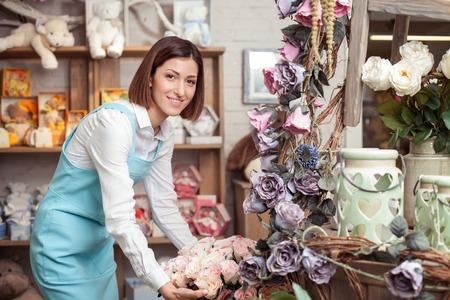 매력적인 여성 꽃집 영감과 꽃다발을하고있다. 그녀는 그녀의 워크샵에 서 웃 고있다. 여성은 행복하게 카메라를 찾고 있습니다