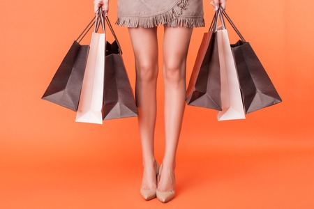 piernas con tacones: Cerca de las piernas femeninas con zapatos de tacones altos. La niña está de pie y sosteniendo muchos paquetes de cosas compradas. Aislado en el fondo de color naranja Foto de archivo