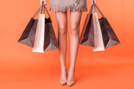 Close-up van vrouwelijke benen met schoenen op hoge hakken. Het meisje bevindt zich en houdt een groot aantal pakjes gekocht dingen. Geïsoleerd op een oranje achtergrond Stockfoto
