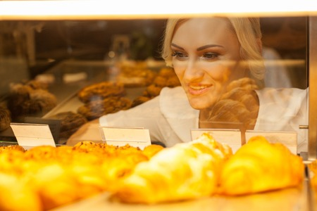 bakery store: Beautiful blond girl is looking at the display of appetite baked products with temptation. She is standing in bakery and smiling Stock Photo