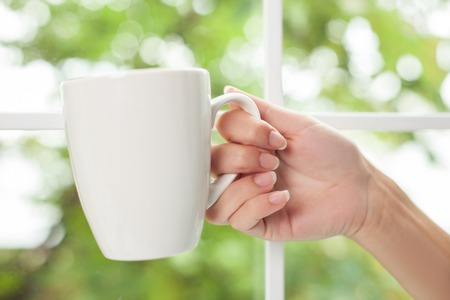 arm holding: Close up of female arm holding a white cup. The girl is drinking coffee Stock Photo