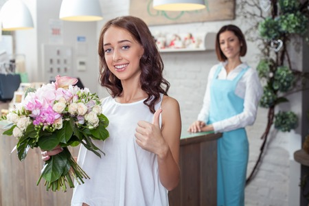 Cheerful girl is buying a cute bouquet in flower shop. She is holding it with joy and giving thumb up positively. She is smiling. The florist is standing with pretty smile on the background Stock Photo