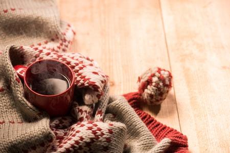 taza: Primer plano de la bufanda caliente de la Navidad y una taza roja de bebida caliente est�n situados en el piso