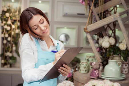 client: Beautiful florist is standing in her flower shop and talking on the phone with her client. She is listening to her customer attentively and smiling. The woman is writing down the main ideas