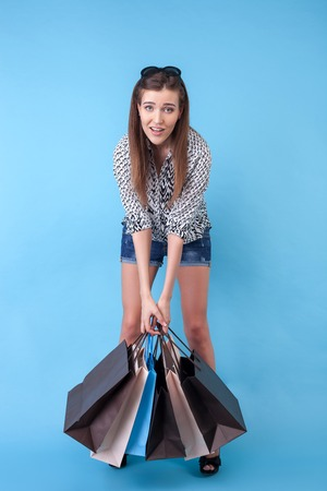 efforts: Beautiful girl is standing and holding heavy packet with efforts. She is tired and exhausted. The lady bought everything. Isolated on blue background