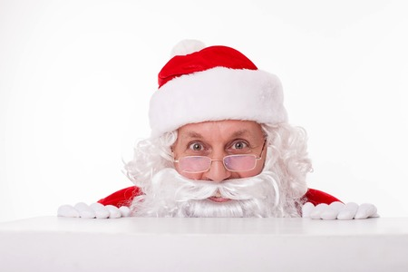 peeping: Old Father Christmas is hiding behind white wall. He is peeping through it with interest. The man is smiling secretly. Isolated on background Stock Photo