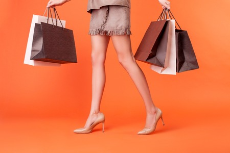 Close up of legs of cheerful girl going to the boutique. She is holding packets of bought things in both her hands. The lady is wearing shoes on high heels. Isolated on orange background Stock Photo