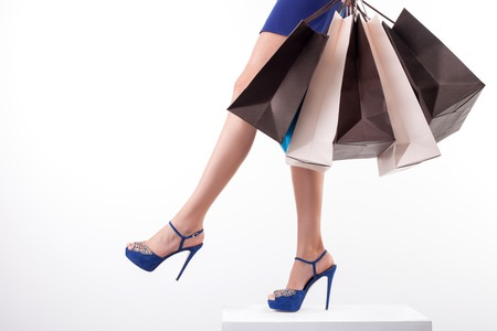 Close up of female legs standing on pedestal. The woman is holding many packets of bought clothing. She is wearing blue sexy shoes on high heels. Isolated on background