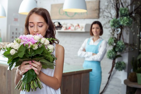 small plant: Beautiful girl is standing in flower shop and holding a bouquet. She is smelling its aroma with pleasure and smiling. A female florist is standing at counter and looking at her with joy